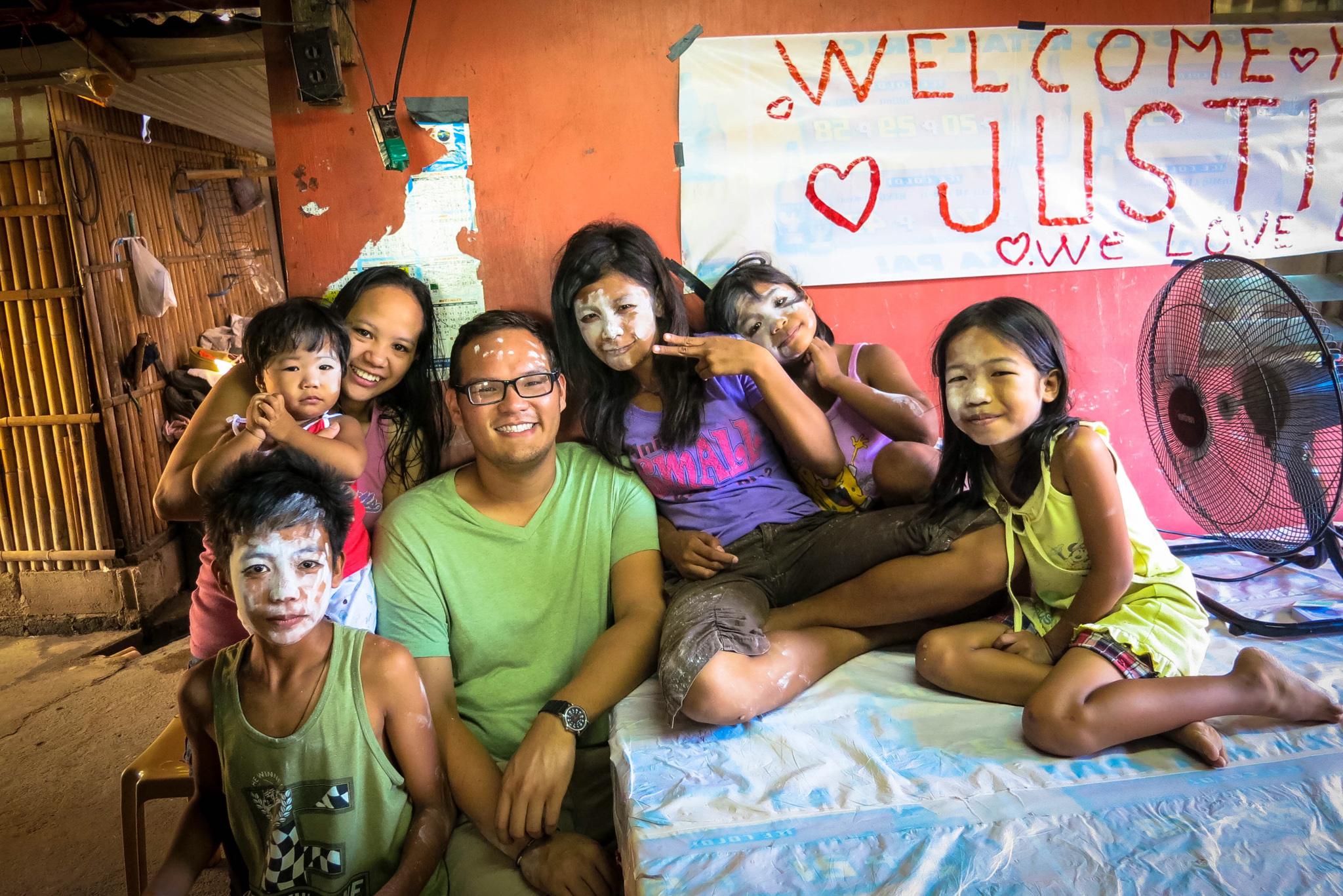 Homem sentado à mesa rodeado por crianças filipinas (Cortesia: Justin Cagaoan)