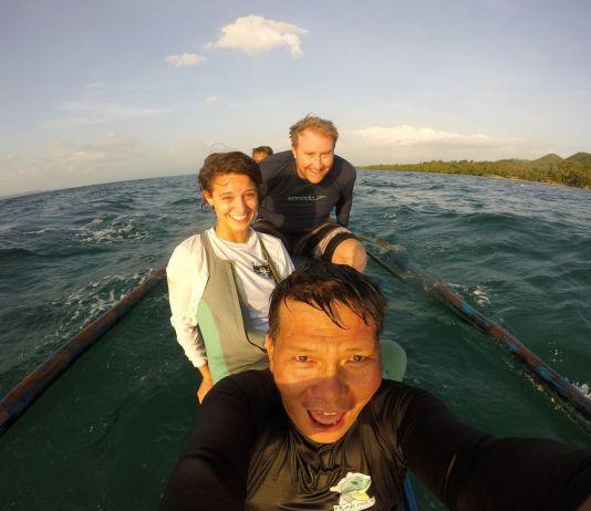 Três pessoas sorridentes em um barco (Corpo da Paz)