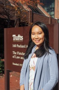 Portrait of woman standing in front of Tufts sign (© Pattariya Jusakul)