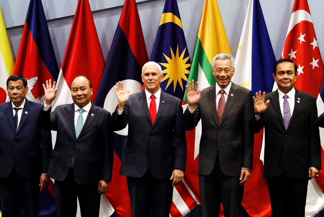 Une rangée de cinq homme debout en train saluant de la main droite, des drapeaux à l'arrière-plan (© Edgar Su/Reuters)