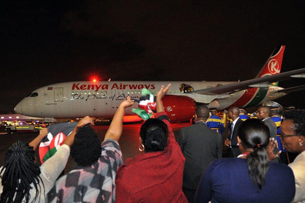 Personas saludan con la mano a un avión en la pista (© Tony Karumba/AFP/Getty Images)