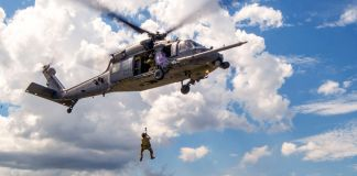 Military man being raised into a flying helicopter (Staff Sergeant Jack Sanders/U.S. Air Force)