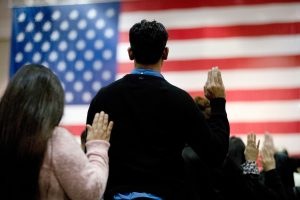 The backside of two people taking an oath in front of an American flag (© Jae C. Hong/AP Images)