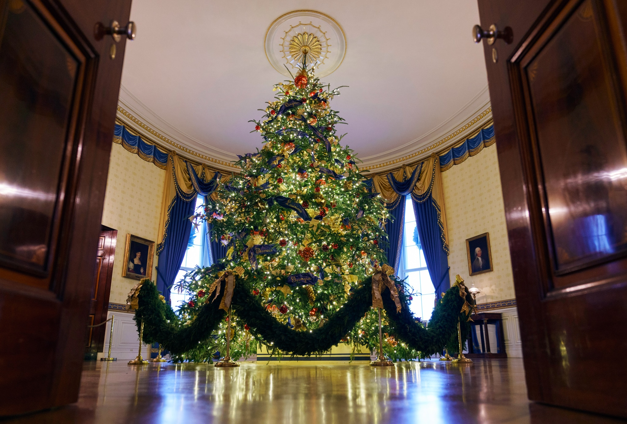 Christmas tree standing in room with blue curtains (©Carolyn Kaster/AP Images)