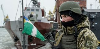 Soldier patrolling ship (© Evgeniy Maloletka/AP Images)