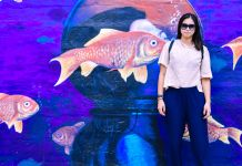 Woman standing in front of a mural of fish in the sea (Courtesy of Michelle Zabat)