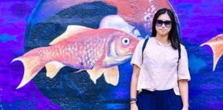 Mujer frente a un mural de peces en el agua (Foto cedida por Michelle Zabat)