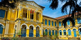 Large yellow building with blue and white trim (© Alamy)