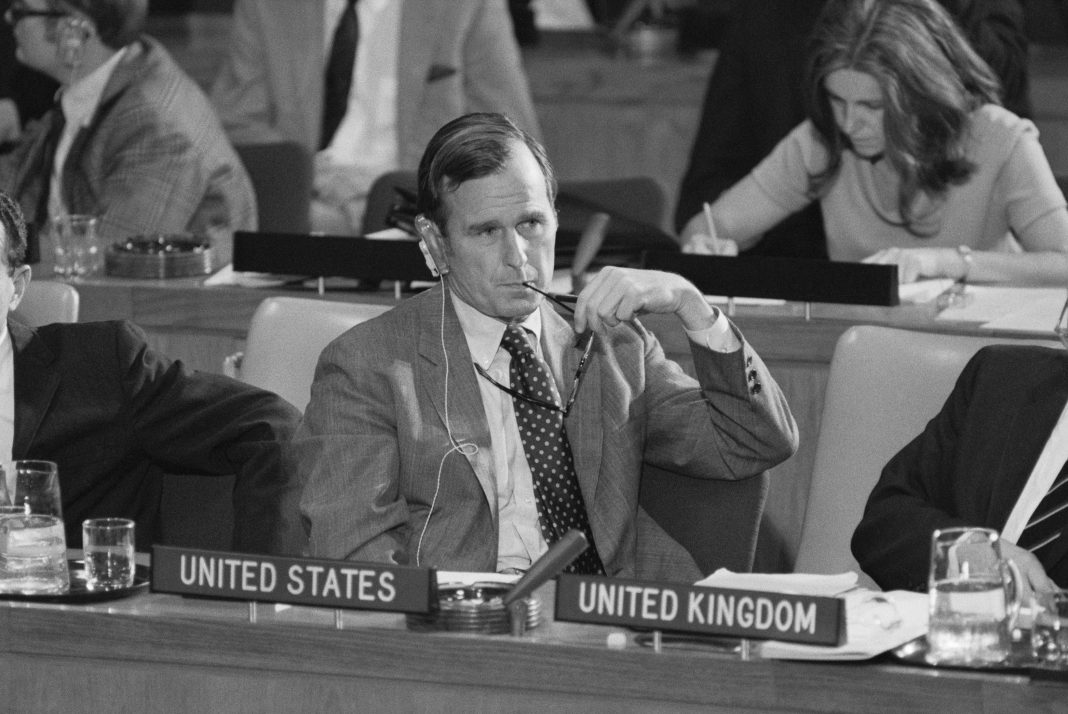 George H.W. Bush at table in front of 'United States' sign (© Bettmann/Getty Images)