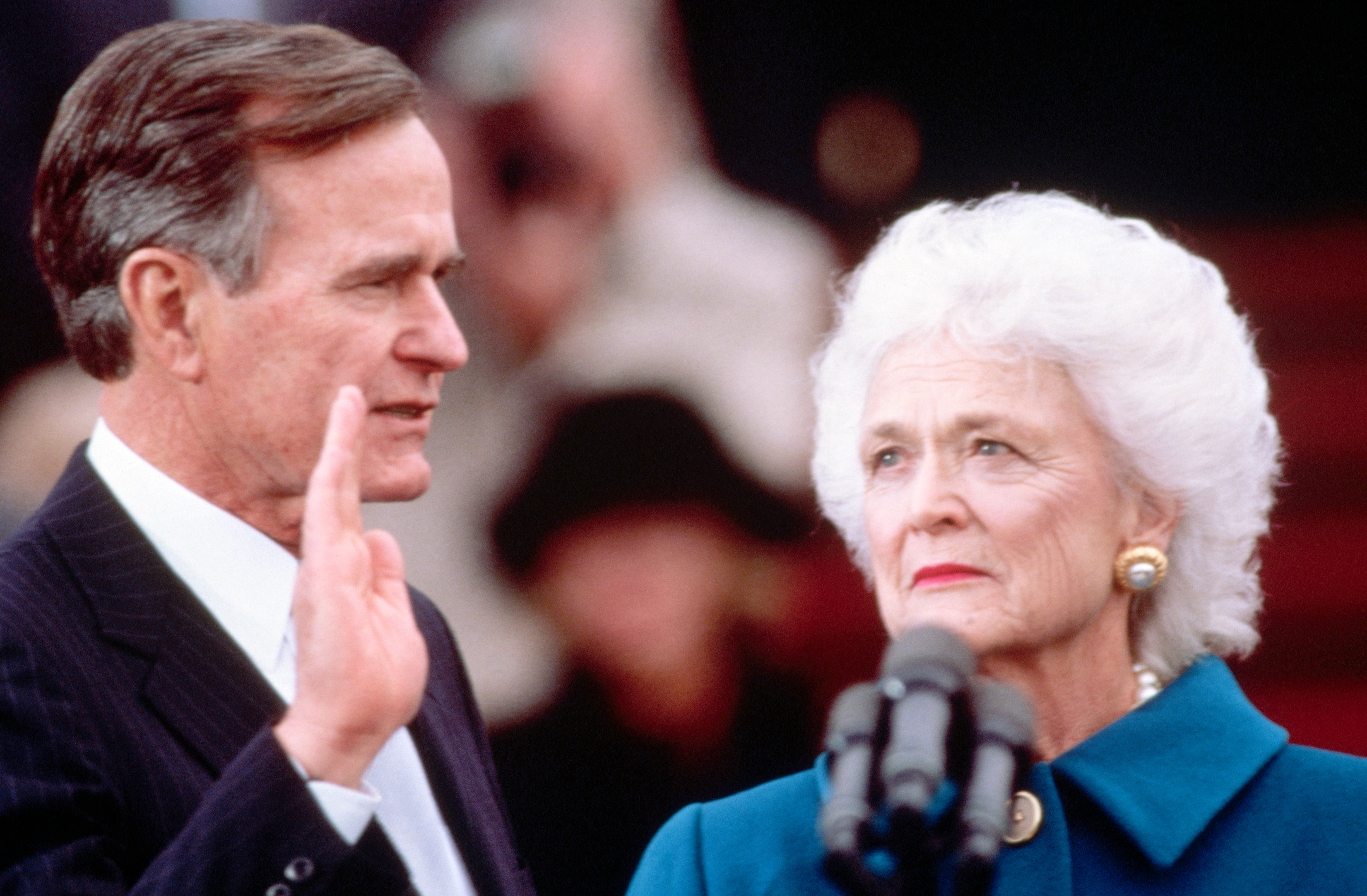 George H.W. Bush with hand raised and Barbara Bush next to him (© Wally McNamee/CORBIS/Corbis via Getty Images)