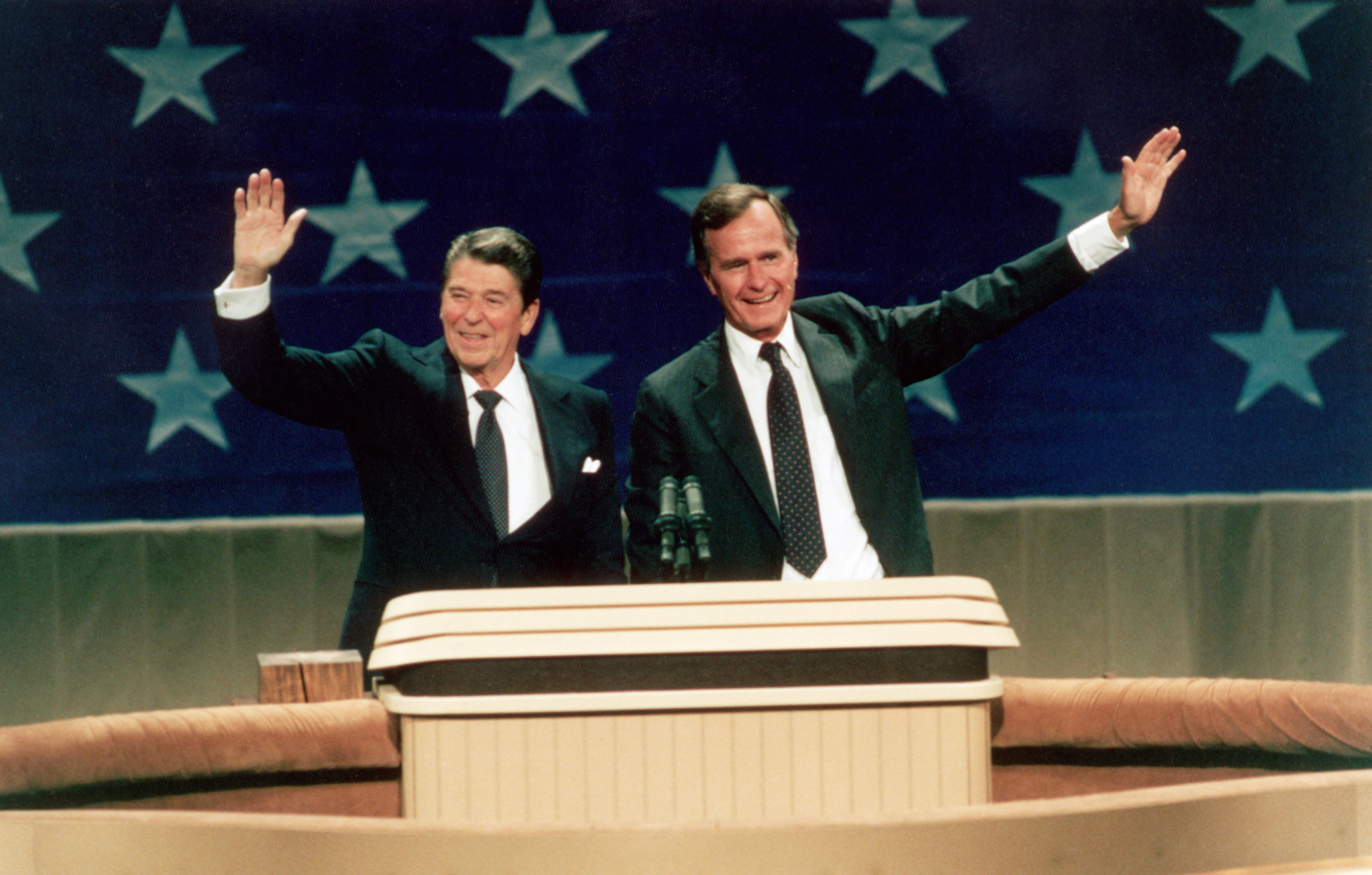 Ronald Reagan and George H.W. Bush at lectern and waving (© Corbis via Getty Images)