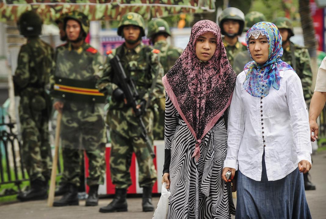 Двое женщин в платках проходят мимо мужчин в военной форме (© Peter Parks/AFP/Getty Images)