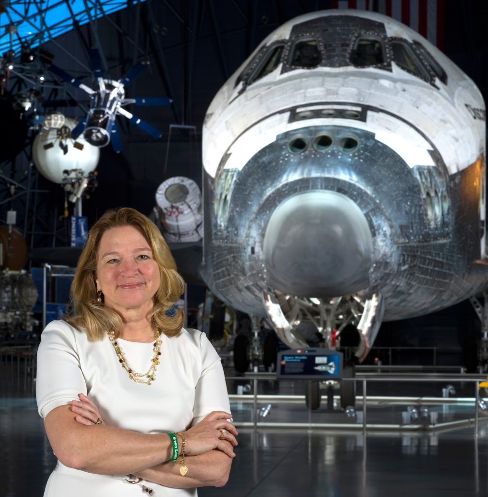 Woman with arms crossed standing in front of space shuttle Discovery (Mark Avino/NASM)