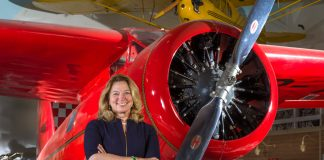 Woman with arms crossed standing in front of red airplane in a museum (Jim Preston/NASM)
