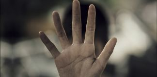 Statistics on human trafficking and photo of hand (State Dept.; Image © Shutterstock / 271 EAK MOTO (/g/eak+moto))