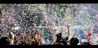 People with upraised arms and confetti in the air
