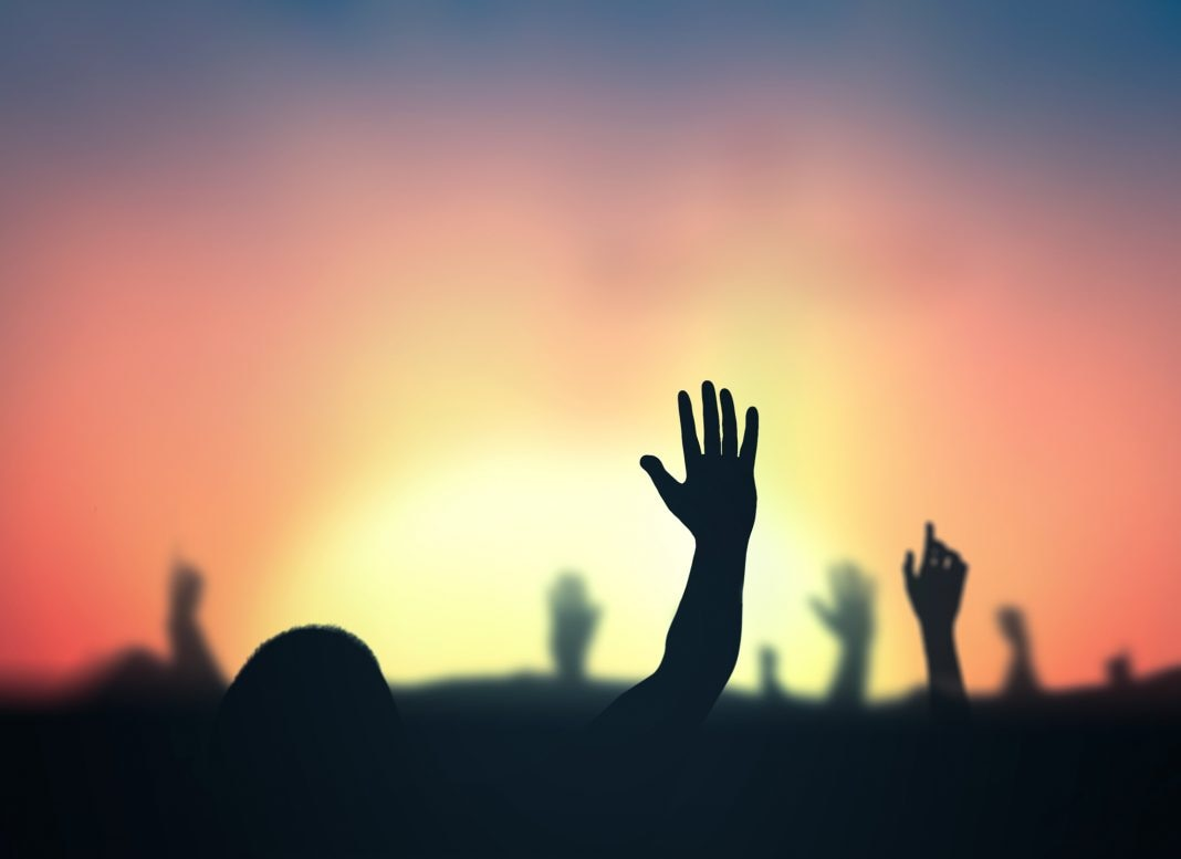 Hands waving into sunset (© Jacob_09/Shutterstock)