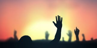 Hands waving into sunset (© Jacob_09/Shutterstock)