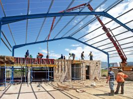 People standing on and near partially constructed building under steel frame (© Shutterstock)