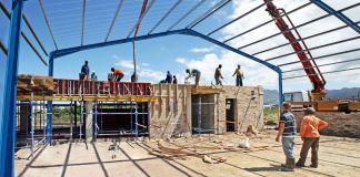 Pessoas paradas em canteiro de obra de edifício sob estrutura de aço (© Shutterstock)