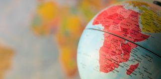 دنیا کے دھندلے نقشے کے سامنے گلوب پر نمایاں دکھائی دیتا ہوا افریقہ کا نقشہ۔ (© Shutterstock)