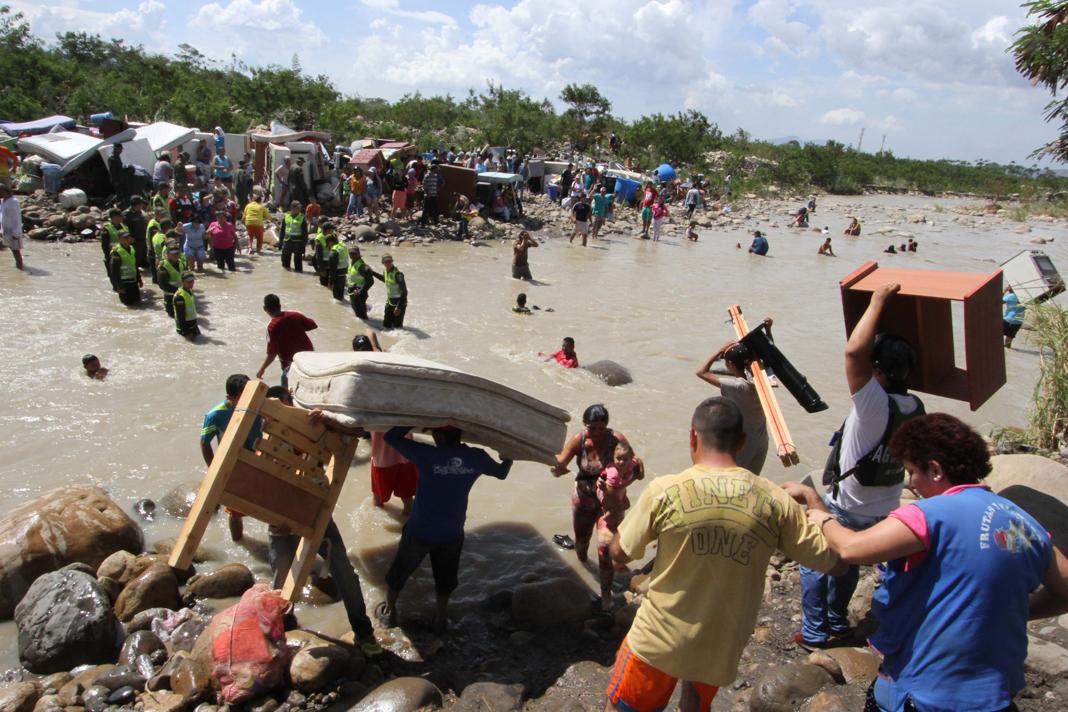 People carrying their belongings across river (© Eliecer Mantilla/AP Images)