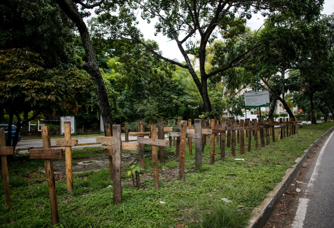 Wooden crosses lining road (© Ariana Cubillos/AP Images)