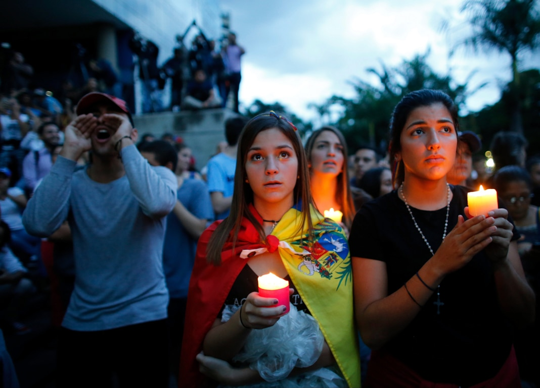 People holding candles (© Ariana Cubillos/AP Images)