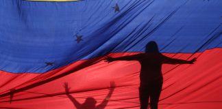Les silhouettes de deux personnes gesticulant, vues à travers un drapeau (© Fernando Llano/AP Images)