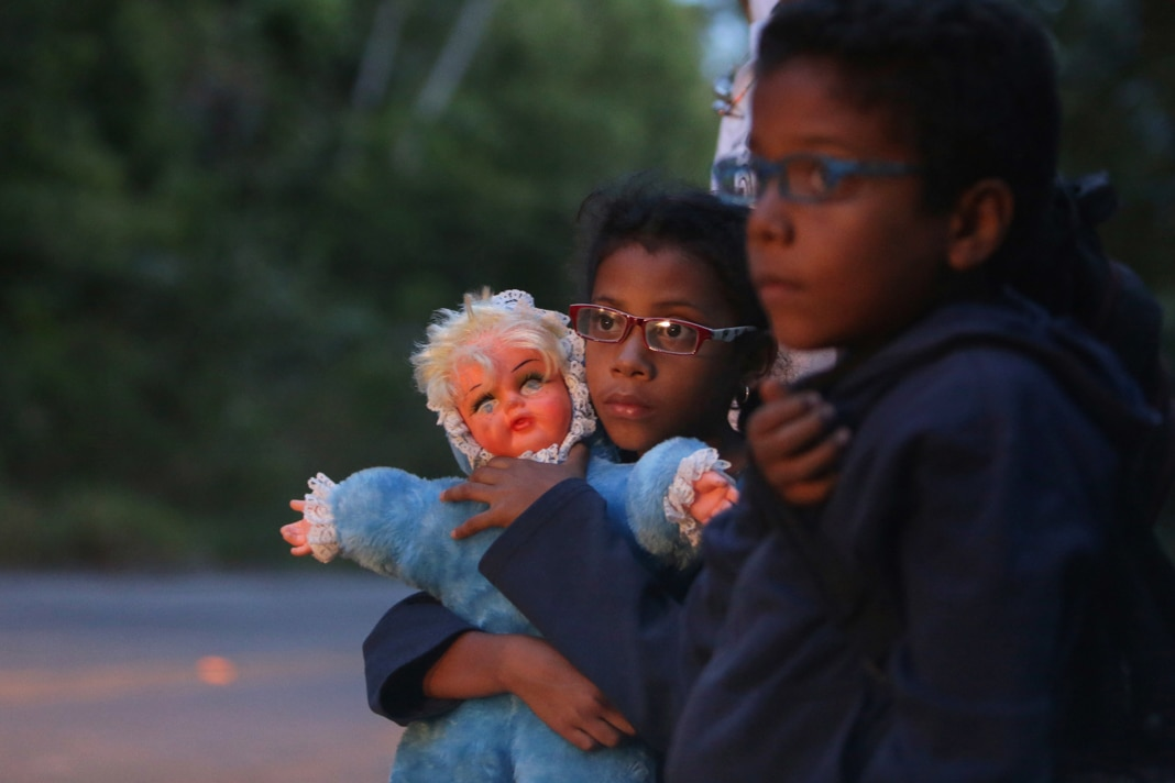 Two children, one with doll, on roadway (© Eraldo Peres/AP Images)