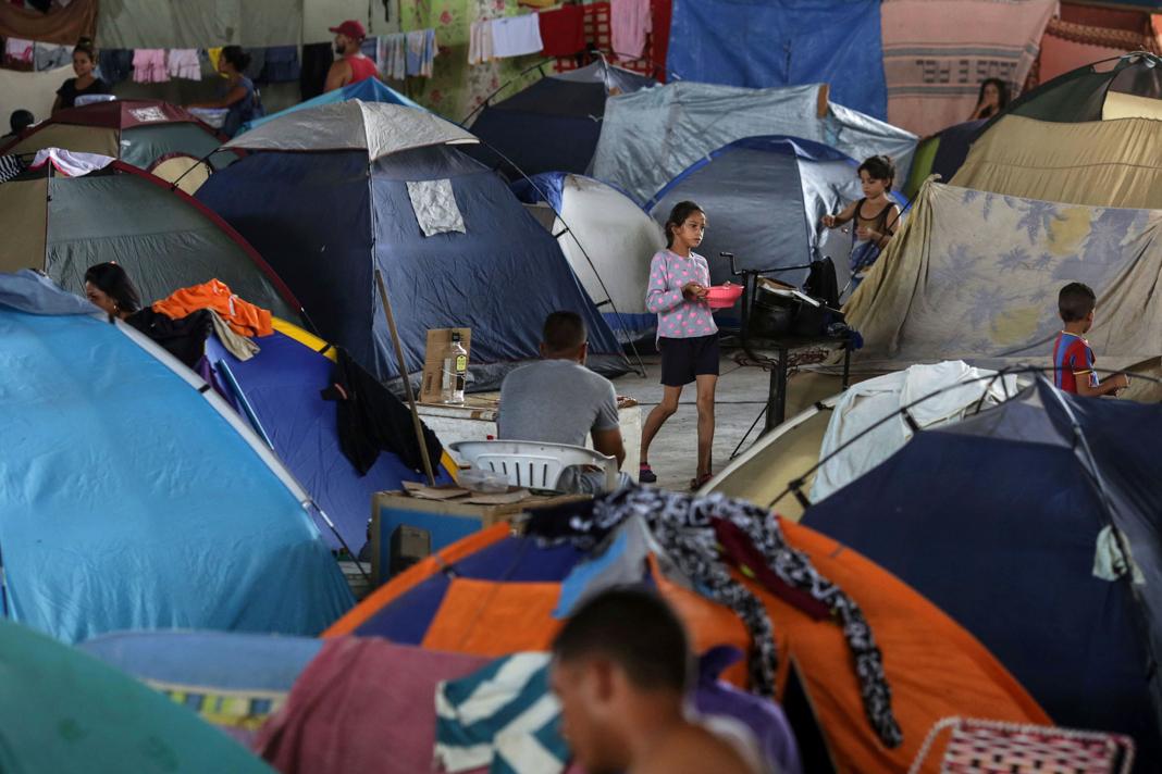 Girl carrying bowl and walking among tents (© Eraldo Peres/AP Images)