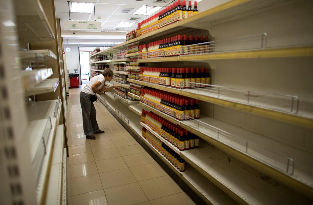 Woman looking at half-filled grocery store shelves (© Ariana Cubillos/AP Images)