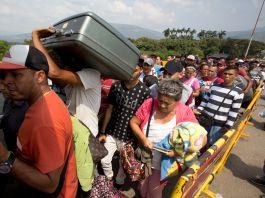 Pessoas alinhadas em via terrestre com seus pertences (© Fernando Vergara/AP Images)