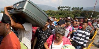 People lining up on the roadway with their belongings (© Fernando Vergara/AP Images)