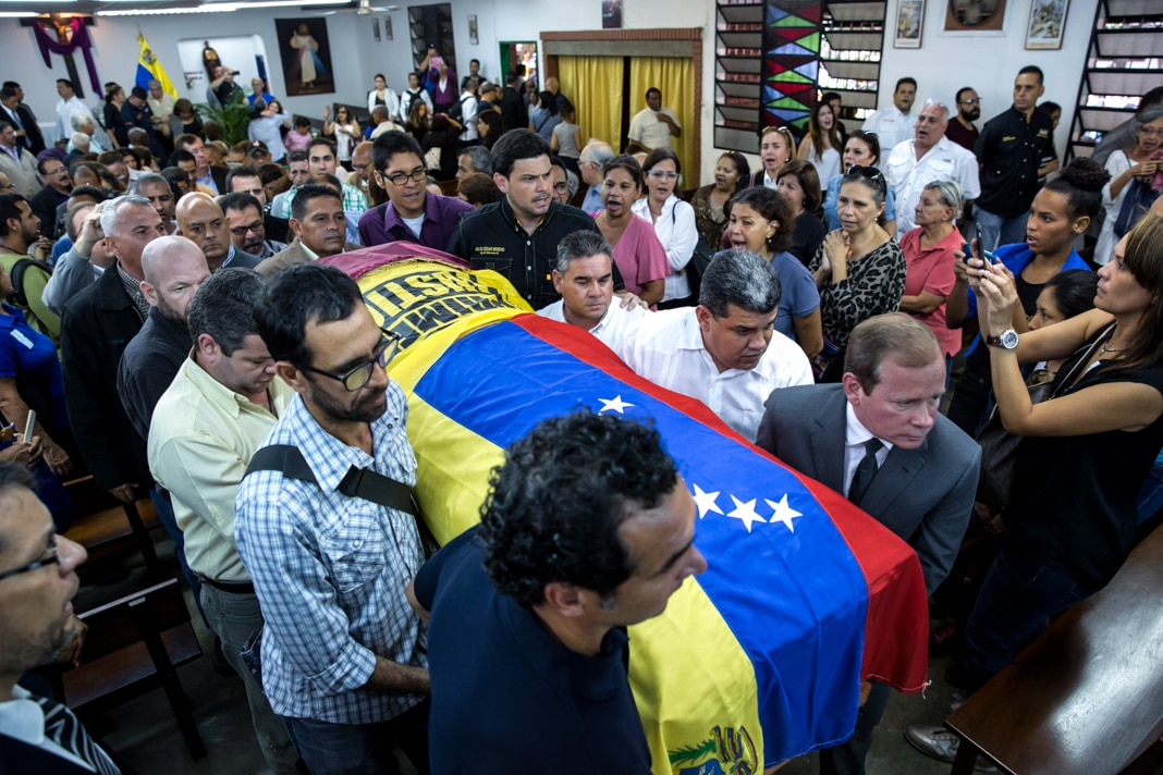 People carrying casket covered in Venezuelan flag through crowd (©Ariana Cubillos/AP Images)