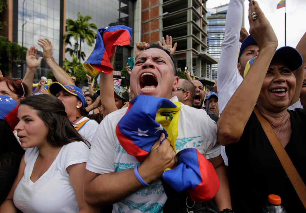 People in street yelling and waving hands (© Boris Vergara/AP Images)