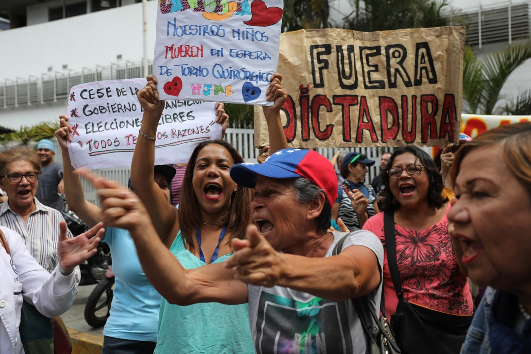 People shouting and waving signs (© Rodrigo Abd/AP Images)