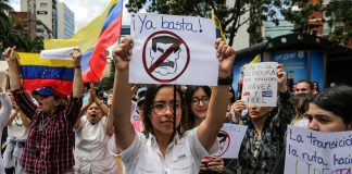 Protesters holding signs (© Fernando Llano/AP Images)
