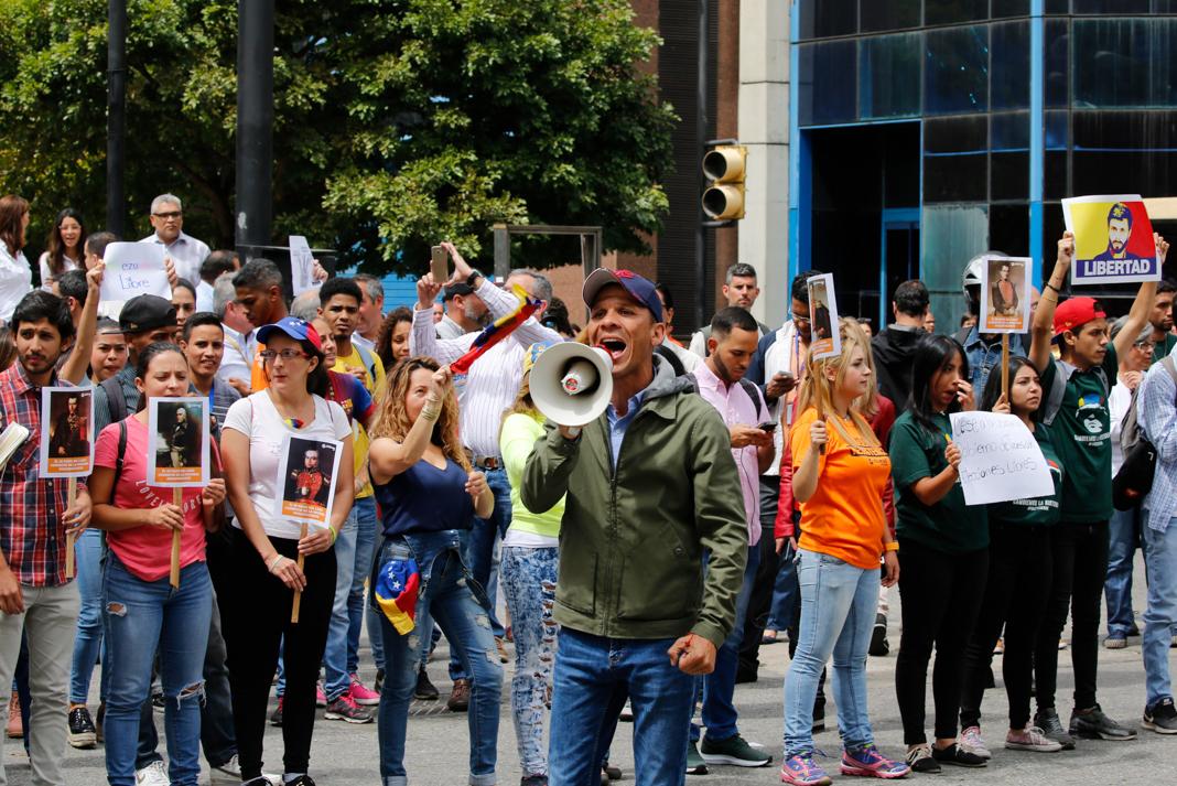 Man shouting into megaphone (© Fernando Llano/AP Images)
