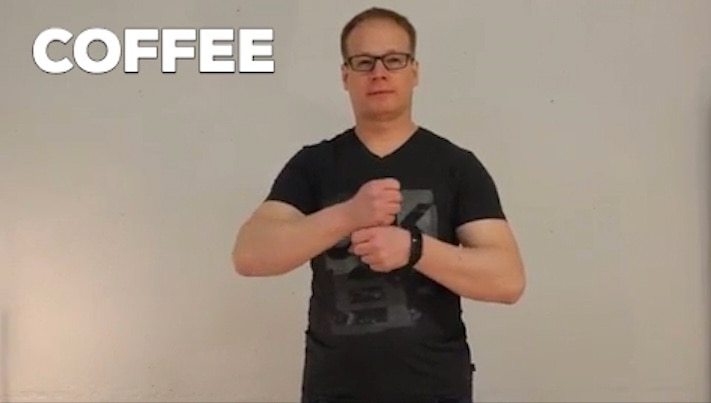 Homem usando linguagem de sinais para descrever café