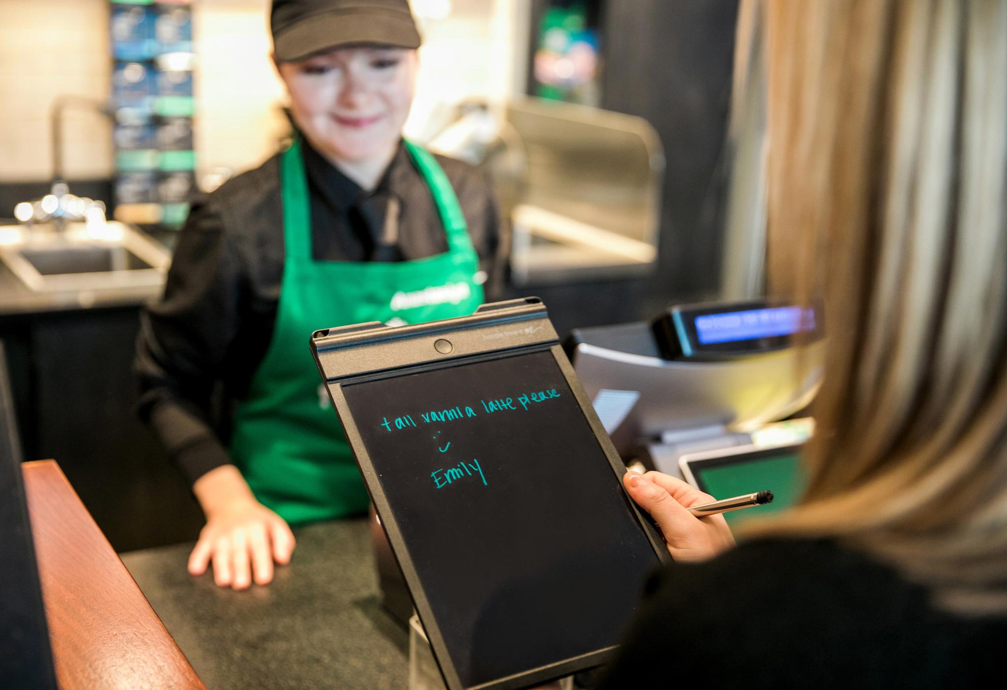 Customer writing drink order on electronic pad in shop (© Joshua Trujillo/Starbucks)
