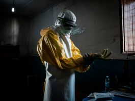 Health worker putting on protective clothing and gloves (© John Wessels/AFP/Getty Images)