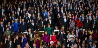 Large group of men and women standing with right hands raised (© Al Drago/Bloomberg/Getty Images)
