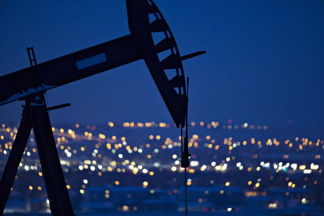 Pumpjack operating above oil well at night (© Daniel Acker/Bloomberg/Getty Images)