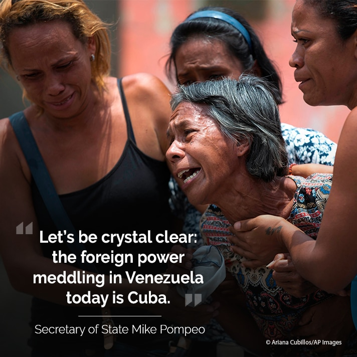 Crying woman being held up by others, with text overlaid (© Ariana Cubillos/AP Images)
