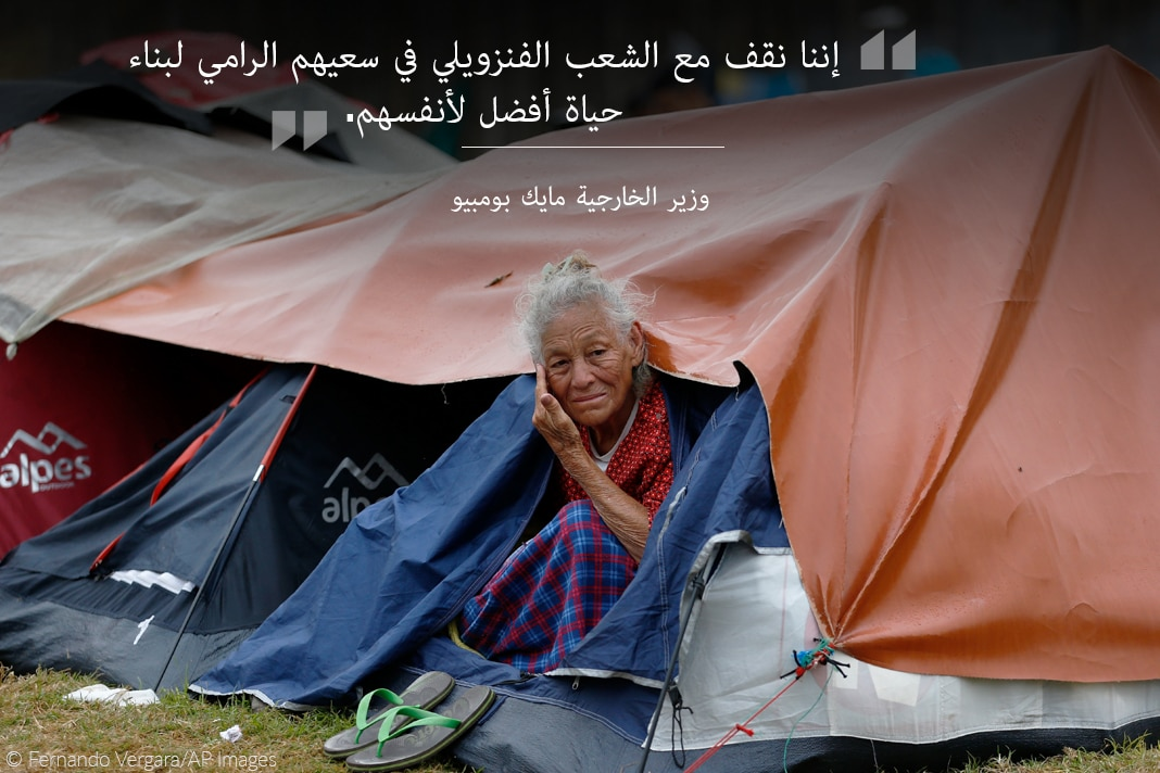 Elderly woman looking out from tent, with text overlaid (© Fernando Vergara/AP Images)