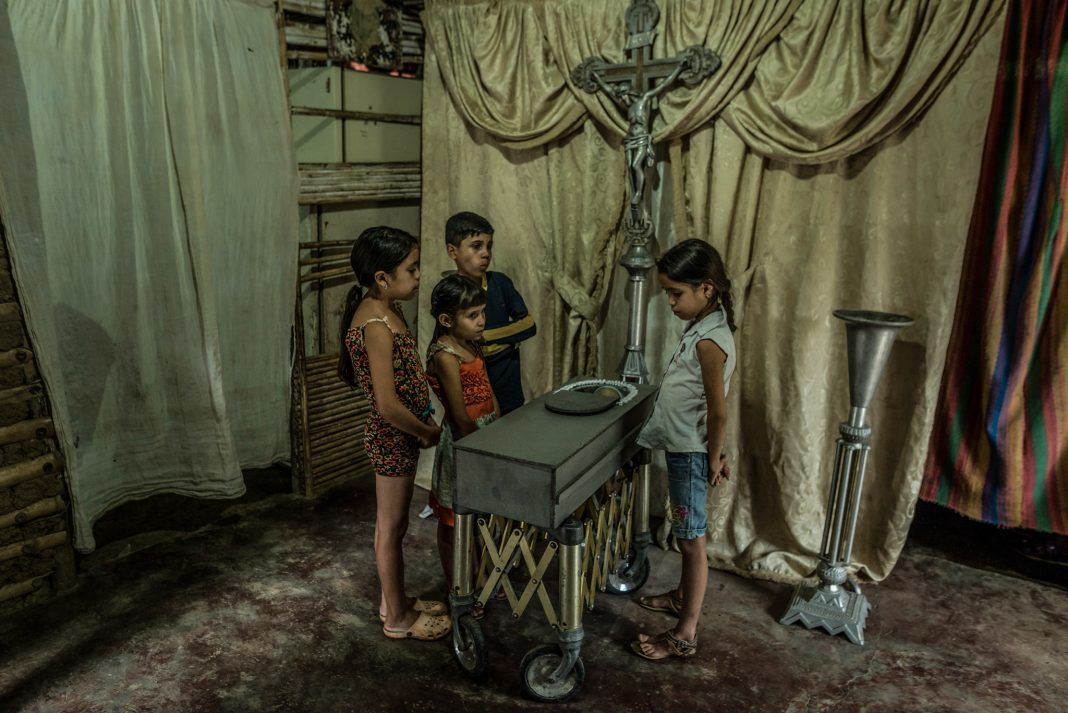 Children viewing body in small coffin (© Meridith Kohut/New York Times/Redux)