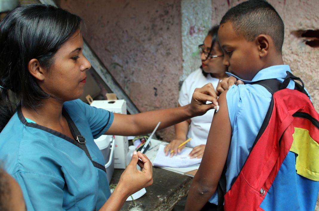 Une femme sur le point de faire une piqûre à un enfant (© Ary Silva/PAHO/WHO)