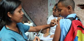 Woman about to inject vaccination needle into a child's upper arm (© Ary Silva/PAHO/WHO)