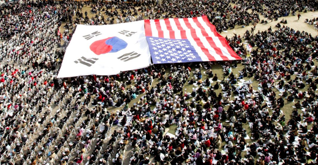 South Korean and U.S. flags spread out amongst a large gathering of people (© Ahn Young-joon/AP Images)